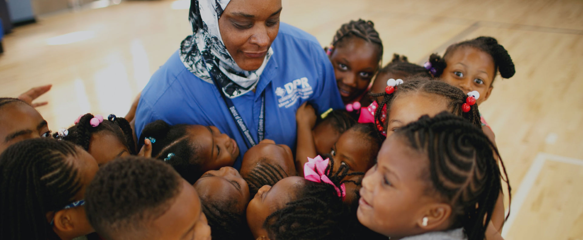 Woman surrounded by smiling children in a school gym