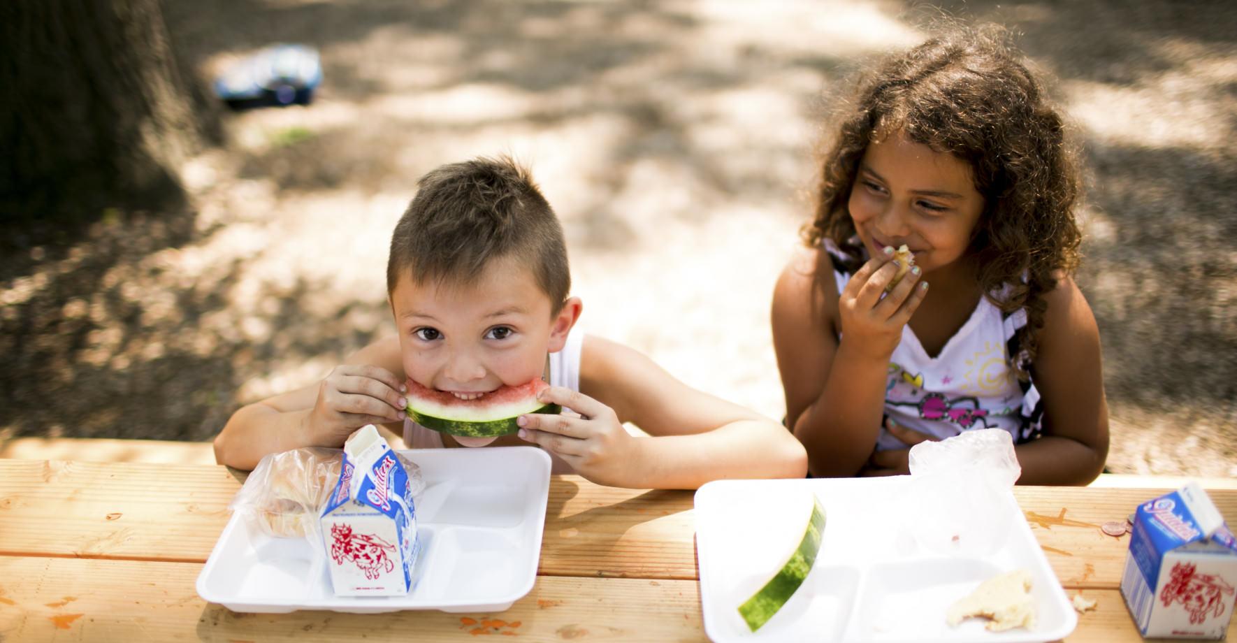 Boy and Girl Eating Watermelon at Picnic Table