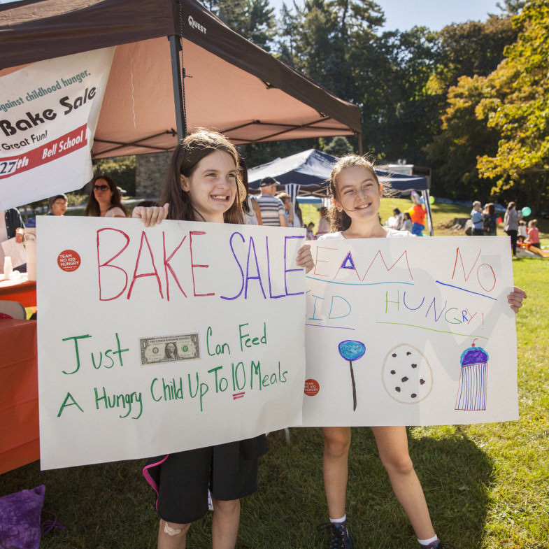 Girls Holding Up Sign for Their Bake Sale