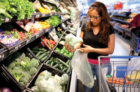 Woman getting broccoli from the produce isle