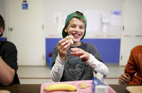 A smiling boy eats a sandwich at school.